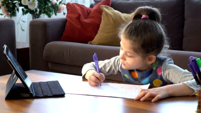 cute little girl writing on white paper. e-learning from home - distant stock videos & royalty-free footage