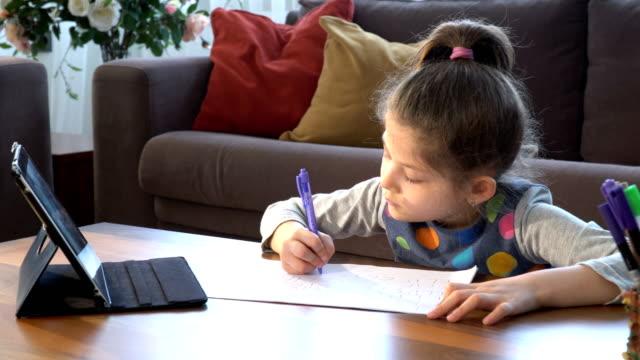 söt liten flicka skriver på vitbok. e-learning hemifrån - avlägsen bildbanksvideor och videomaterial från bakom kulisserna