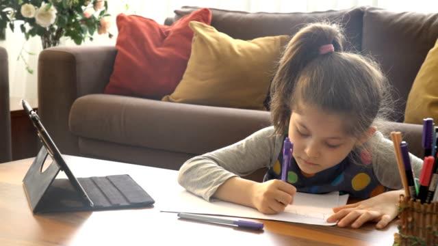stockvideo's en b-roll-footage met het leuke meisje dat op wit document schrijft. e-learning vanuit huis - e learning