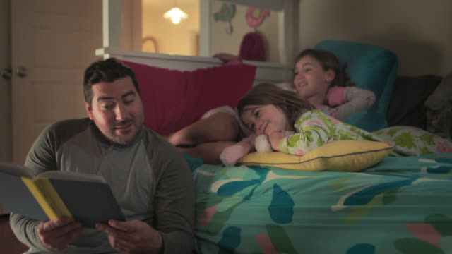 ws. cute little girl yawns and smiles at her sister as father reads bedtime story. - ora di andare a letto video stock e b–roll