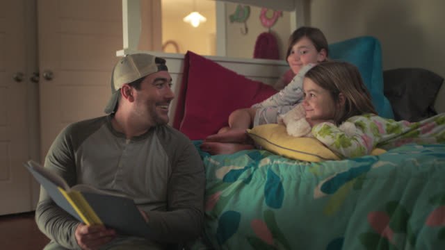 vidéos et rushes de ws. cute little girl yawns but promises she's not sleepy as dad reads bedtime story book. - histoire