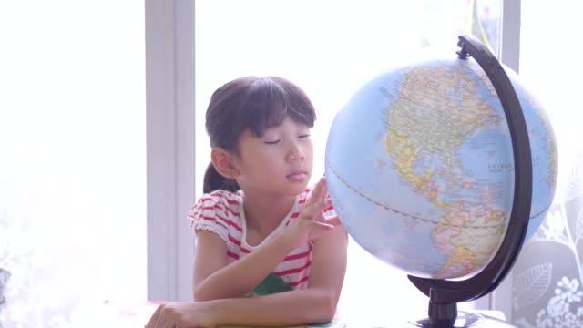 cute little girls looking at globe. - mappamondo video stock e b–roll
