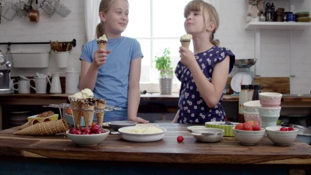 cute little girls preparing ice cream with toppings in a cone 4k video - serving size stock videos & royalty-free footage