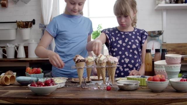 ragazze carine che preparano il gelato con condimenti in un video cono 4k - cibi surgelati video stock e b–roll