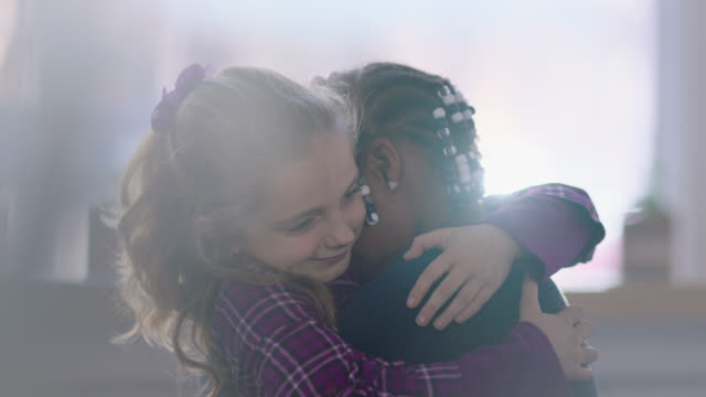 ms slo mo. cute little girls share a sweet hug in local cafe. - gruppo multietnico video stock e b–roll