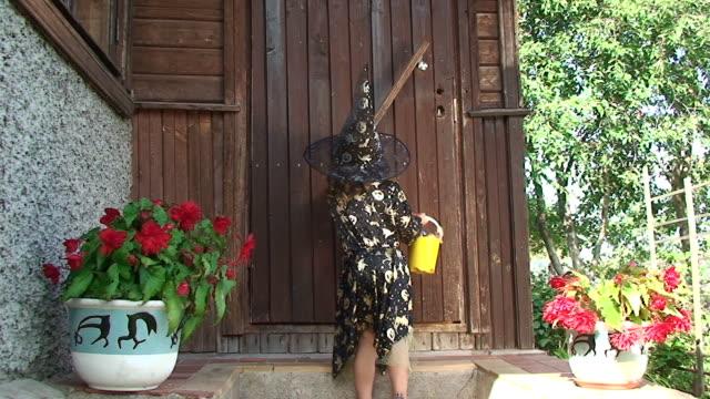 Cute little Halloween girl knocking in the door