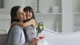 Cute little kid daughter congratulating happy mom with mothers day