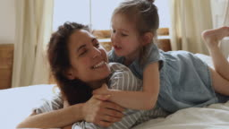 Cute little kid daughter embrace kiss mom lying on bed