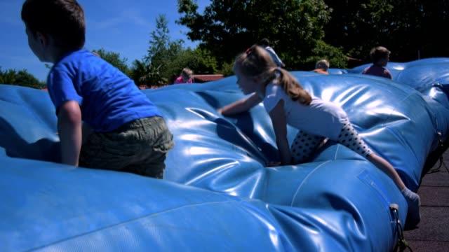かわいい子供の遊び場に巨大な空気の枕の上のジャンプ - 屋外遊具点の映像素材/bロール