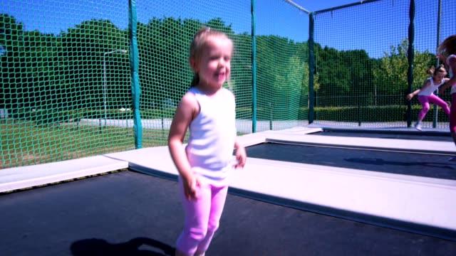stockvideo's en b-roll-footage met schattig weinig kinderen springen op de trampoline - trampoline
