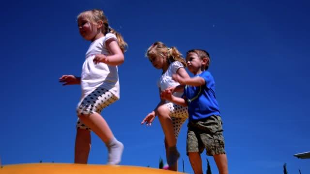 stockvideo's en b-roll-footage met weinig leuke kinderen spelen op een speelplaats - trampoline