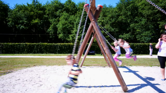 Cute little Kids Playing On a Swing in a Park Playground