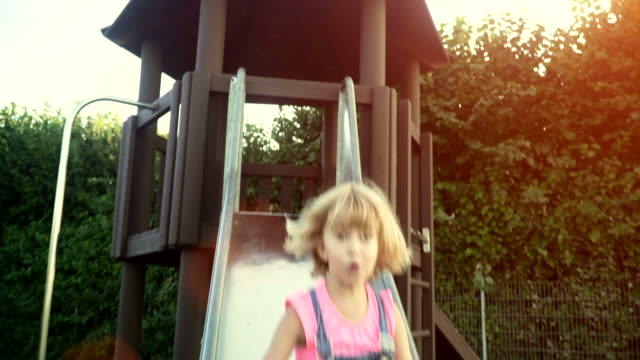 Cute little kids playing on playground slide