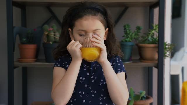 夏の日にバルコニーでオレンジジュースを飲むので、カメラを見てかわいい - 女児1人点の映像素材/bロール