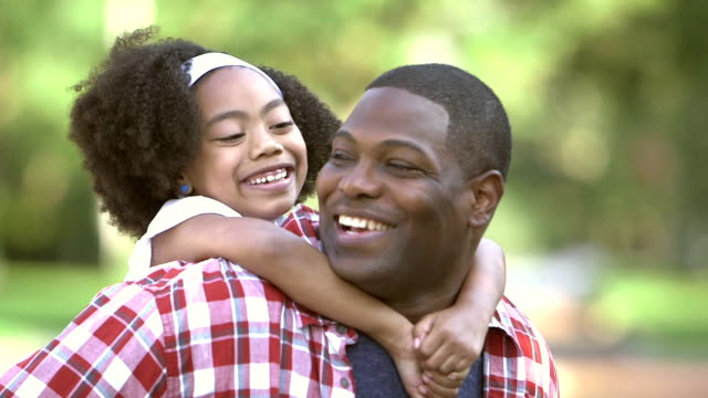 cute little mixed race girl on father's back - single father stock videos & royalty-free footage