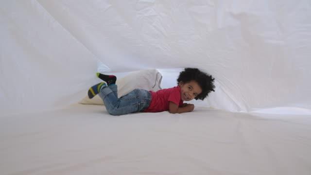 cute little more boy playing beneath sheet on bed - verstecken stock-videos und b-roll-filmmaterial