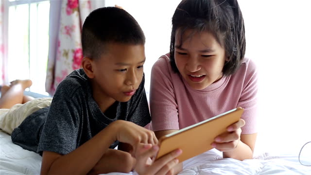 Niedliche kleine spielen auf Tablet im Bett