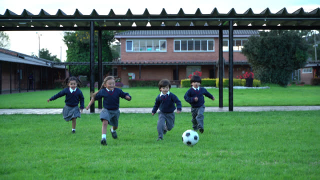 cute little students playing with a football at the school playground - school yard stock videos & royalty-free footage
