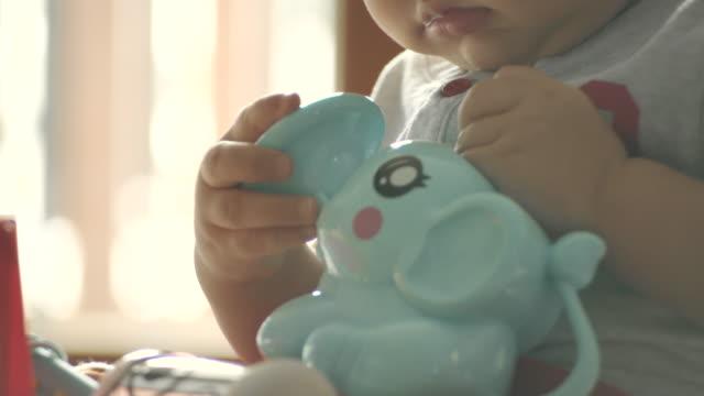nettes kleines kleinkind junge mit spaß spielen mit kunststoff-spielzeug - 6 11 monate stock-videos und b-roll-filmmaterial