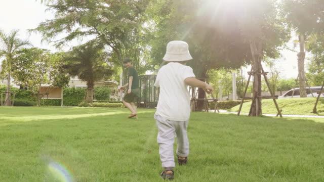 Cute little toddler boy running in green grass in park