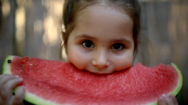 Cute little toddler eating a slice of watermelon