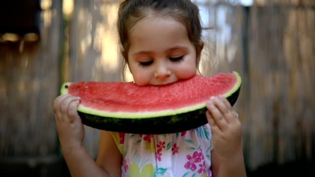 vidéos et rushes de mignon petit enfant en bas âge manger une tranche de pastèque - petites filles