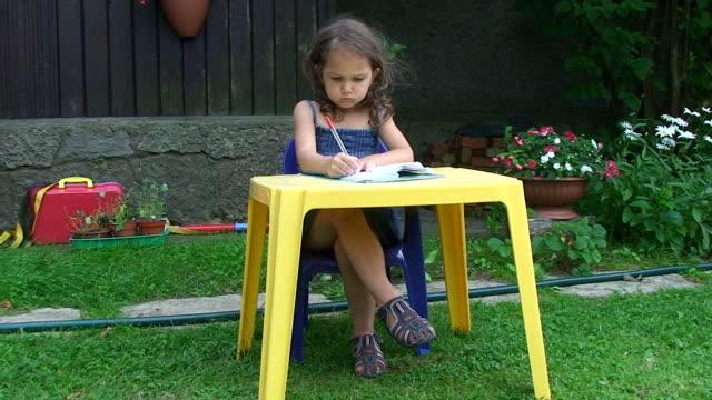 vidéos et rushes de mignon «little fille apprendre à écrire dans le jardin - table de pique nique