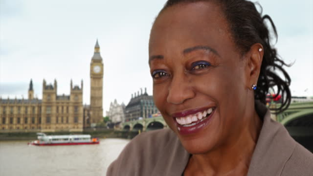 cute mature black woman near big ben smiling and laughing at camera - big ben点の映像素材/bロール