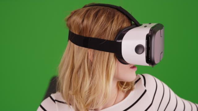 cute millennial girl wearing vr headset for fun entertainment on green screen - schutzbrille freisteller stock-videos und b-roll-filmmaterial