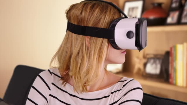 cute millennial girl wearing vr headset for fun entertainment - schutzbrille freisteller stock-videos und b-roll-filmmaterial