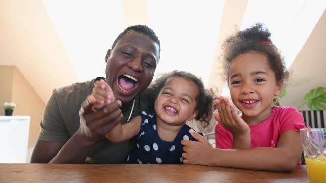 stockvideo's en b-roll-footage met leuke gemengde familie van het ras die op een videovraag glimlacht - bewegend beeld