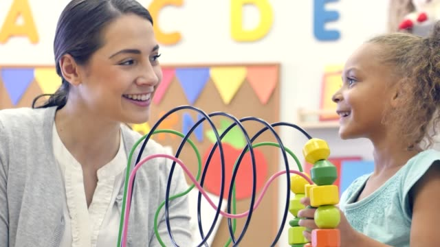 cute mixed race female preschool student plays with bead maze - child care stock videos & royalty-free footage