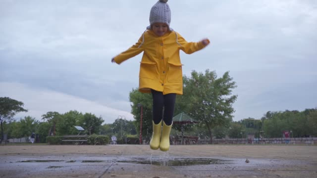 cute playful girl having fun in a puddle of water outdoors in autumn - raincoat stock videos & royalty-free footage