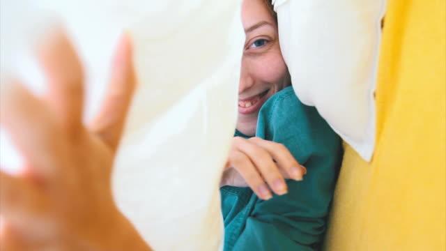 Cute playful girl under the sheet