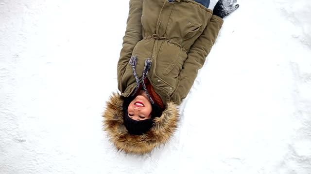 Leuke positieve meisje liggend In de sneeuw