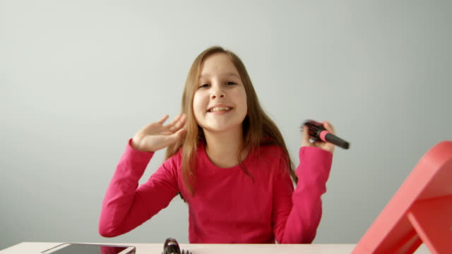 cute pre-teen child vlogger recording video online for vlog channel on social media while brushing her hair with a brush shot on red camera - brushing hair stock videos & royalty-free footage