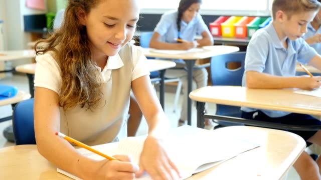 Süße private Grundschule Schülerin arbeitet auf Dienstreise in Klasse