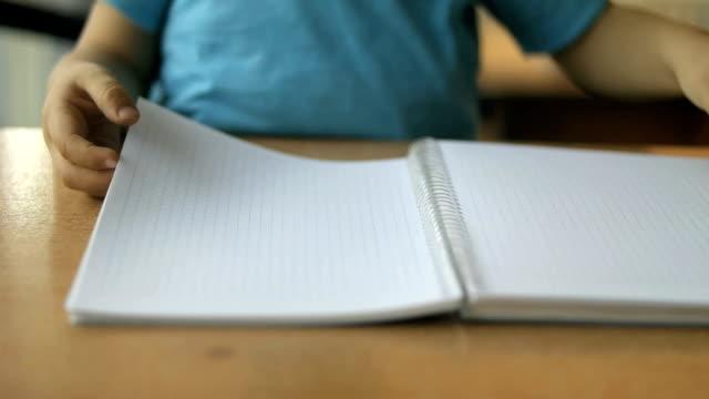 vidéos et rushes de adorable élève écrit au bureau - carnet