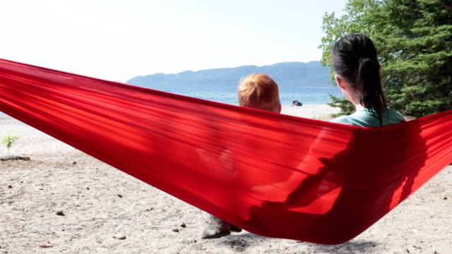 nettes rothaarige kind mit spaß in red hammock auf dem campingplatz im sommer - resting stock-videos und b-roll-filmmaterial