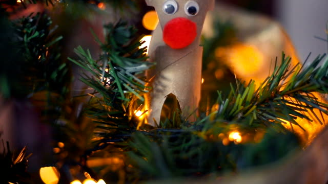 Cute reindeer with red nose, made by hand, decorating a Christmas tree.