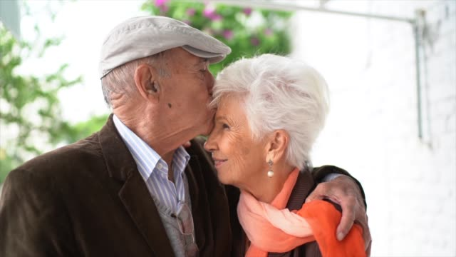 cute senior couple looking at each other while embracing - white cap stock videos & royalty-free footage