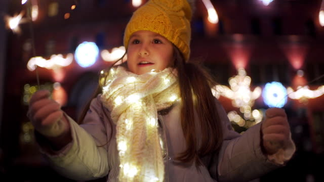 cute serene child celebrating a new year outdoors in the city - christmas decoration stock videos & royalty-free footage