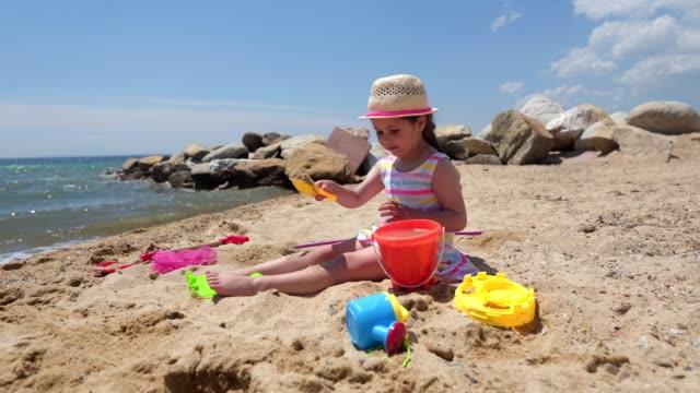 vídeos y material grabado en eventos de stock de lindo niño sereno jugando en la arena en la playa - accesorio de cabeza