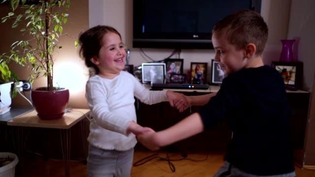 Cute siblings bonding and dancing at home