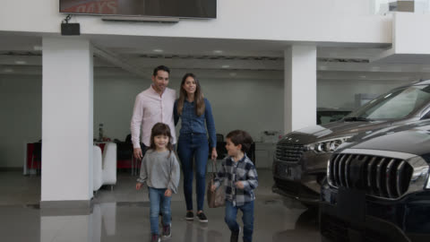 cute siblings running at a car dealership towards a car they liked pointing it to loving mom and dad - new stock videos & royalty-free footage