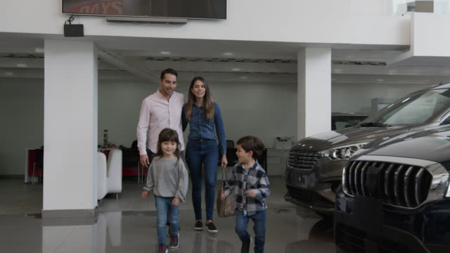 cute siblings running at a car dealership towards a car they liked pointing it to loving mom and dad - family with two children stock videos & royalty-free footage