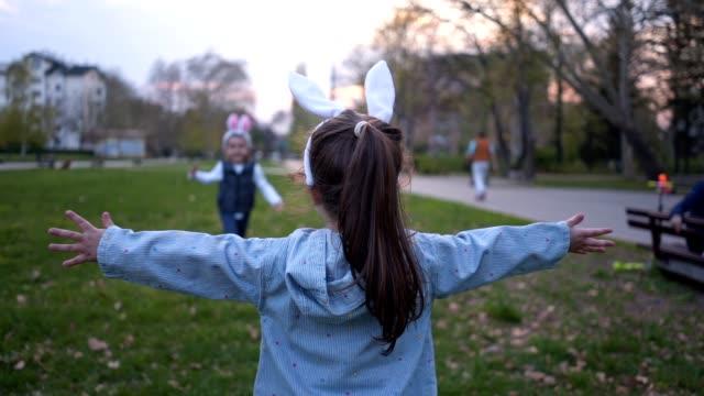 vídeos y material grabado en eventos de stock de lindos hermanos con orejas de conejo en pascua - brazos estirados