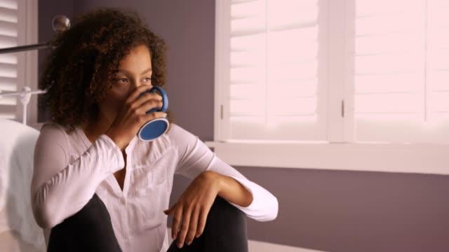 vídeos y material grabado en eventos de stock de cute single woman sitting on bedroom floor contemplating.  attractive young black woman thinking and drinking from coffee cup. 4k - articulación humana