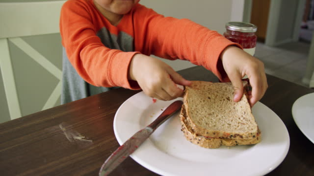a cute six year-old caucasian boy puts two halves of a peanut butter and jelly sandwich together on a plate and then picks it up and takes a bite out of it at a kitchen table indoors - self sufficiency stock videos and b-roll footage