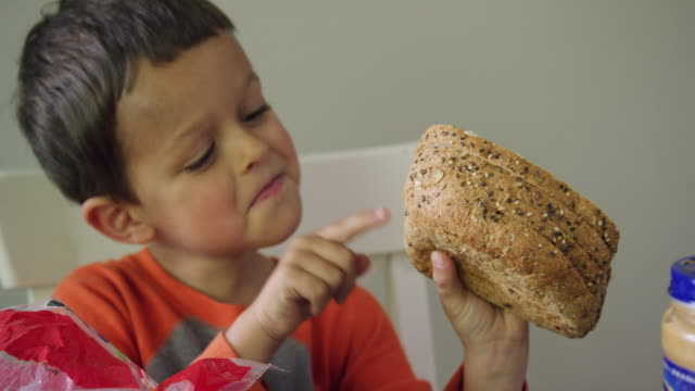 a cute six year-old caucasian boy removes several pieces of bread from the loaf bag and uses his finger to count them in preparation for making a sandwich while acting playful at a kitchen table - making a sandwich stock videos and b-roll footage